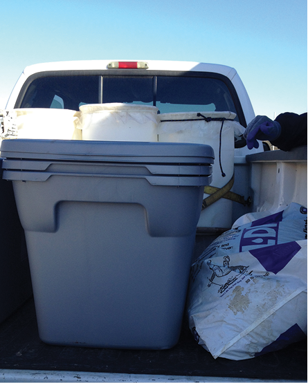 A pickup truck bed with plastic storage bins and a bag of absorbent material.