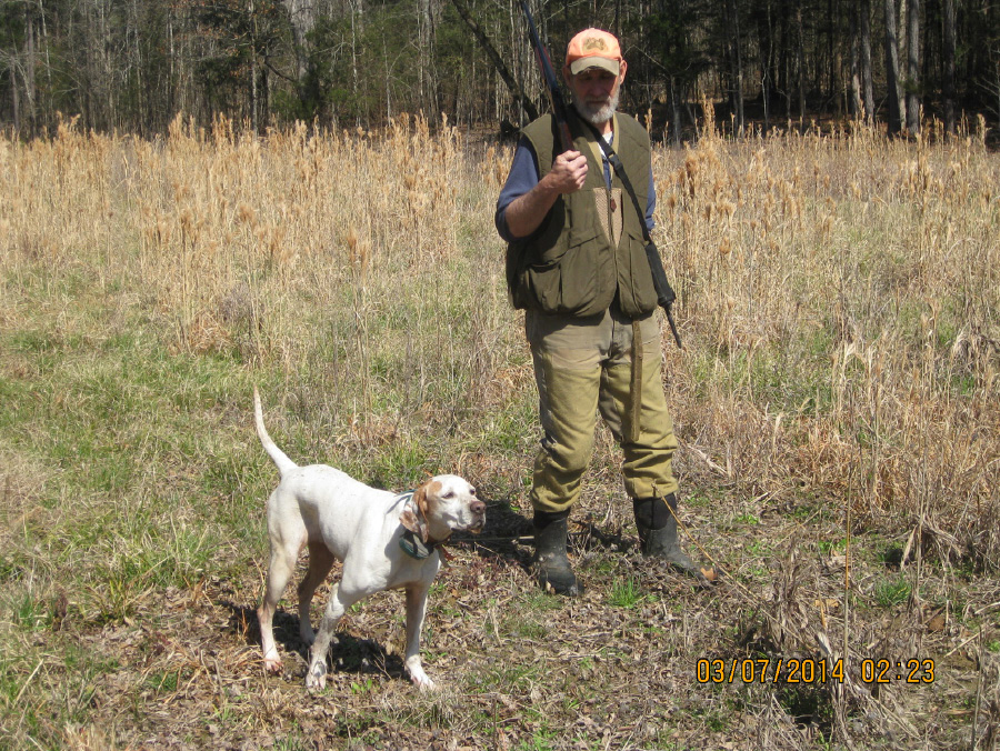 A hunter makes a hand signal to a hunting dog.