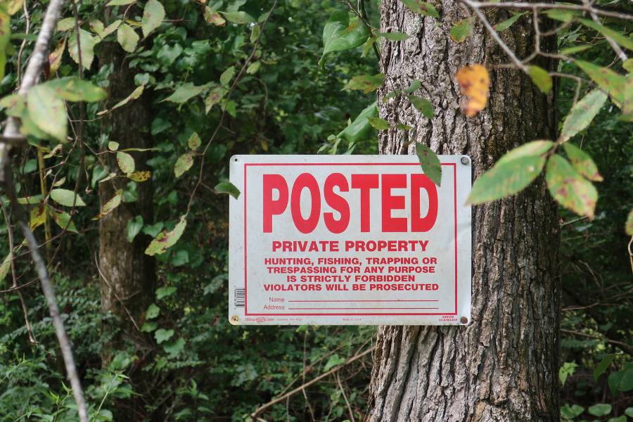 "A sign attached to a tree in the woods. It reads, ""Posted: Private property. Hunting, fishing, trapping, or trespassing for any purpose is strictly forbidden. Violators will be prosecuted."""