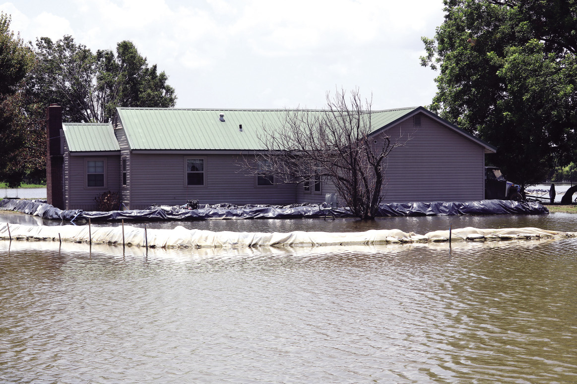 A house has one barrier near its foundation and another barrier farther out away to protect it from the flood.