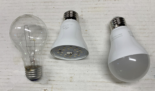 Three lightbulbs on a white cardboard background.
