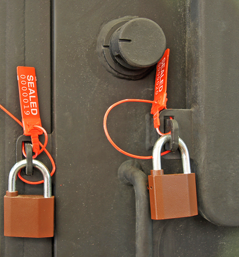 "Two padlocks on a delivery truck door. Each lock has an orange tag with the word ""sealed"" followed by a seven-digit number."