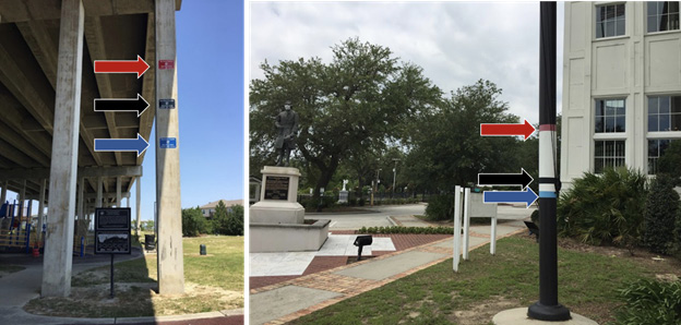 Two poles showing high water marks in two different communities. Each pole has red, black, and blue water marks for that particular community.
