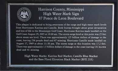 A dedication plaque with information about the effects of Hurricanes Katrina and Camille on the Mississippi Gulf Coast.