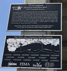 Two plaques on a building support beam with information on the High Water Marks Initiative and the impacts of Hurricanes Camille and Katrina on the Mississippi Gulf Coast.