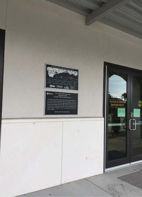 Two plaques on the wall beside an entry door to the D'Iberville Water and Sewer Department.