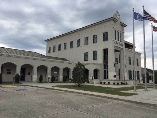 A large building with a parking lot and three flagpoles in front.