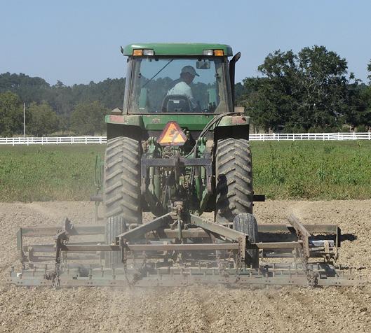 A tractor pulls an implement across a dirt field.