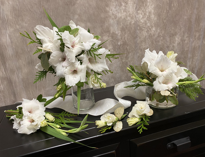 Two floral arrangements in vases, a small arrangement, and two boutonnieres displayed on a dark cabinet. The white flowers are accented with greenery.