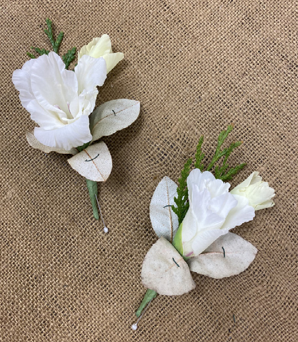 Two white flowers with sprigs of greenery and three small leaves attached together. The leaves have very small, single stitches of wire holding them in place.