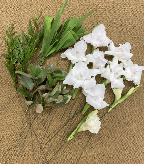 Three types of greenery and several white flowers attached to wires.
