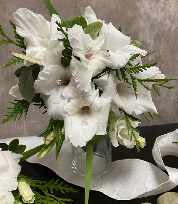 A bouquet of white flowers and small pieces of greenery in a glass vase.