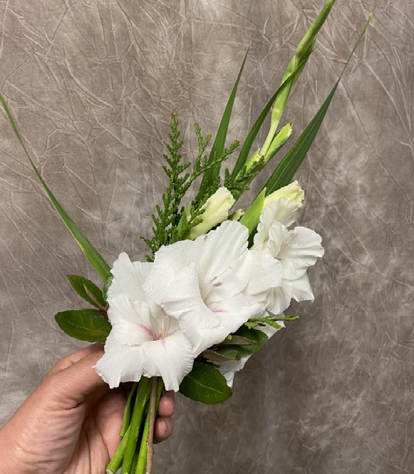 A person's hand holds a small bouquet of white flowers and greenery.