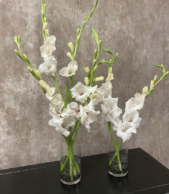 Two small glass vases with dark rocks and three or four stalks of white flowers in each vase.