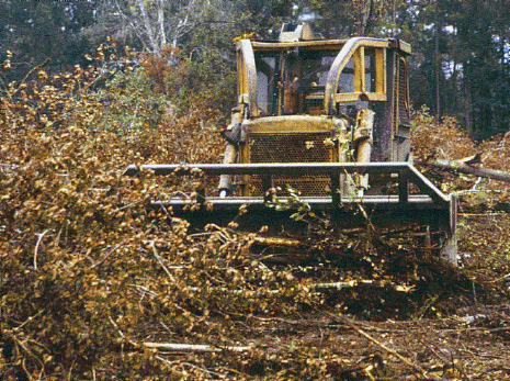 A tractor is raking debris into piles or rows as part of the mechanical site preparation technique.