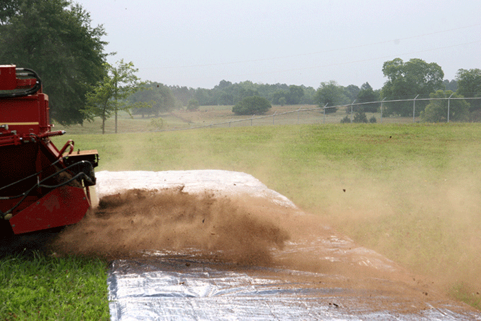 Image of a spreader spreading litter over a tarp, demonstrating step 2