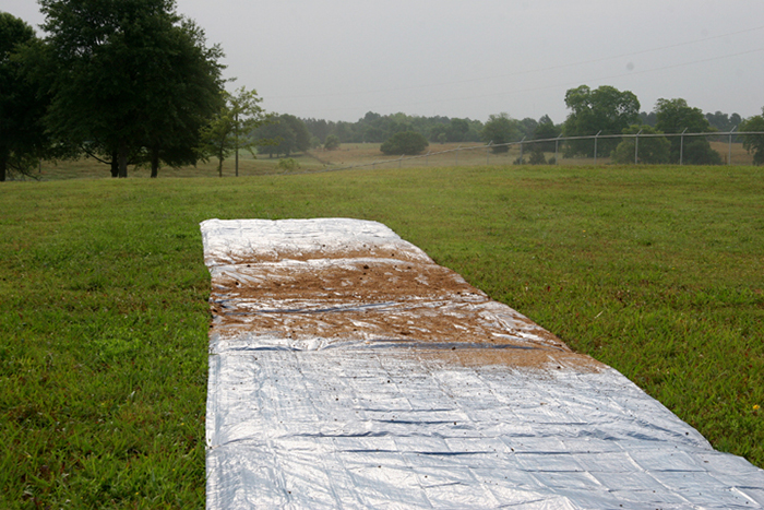 A tarp spread with poultry litter n a green field.
