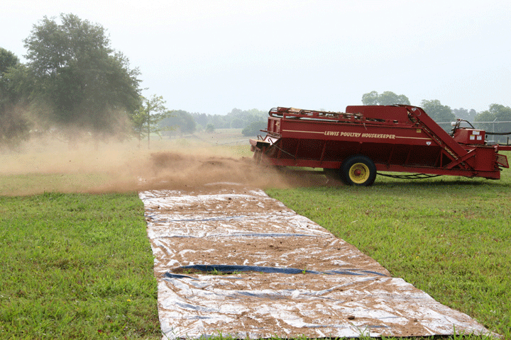 Image of a spreader spreading litter over a tarp, demonstrating the second part of step 4