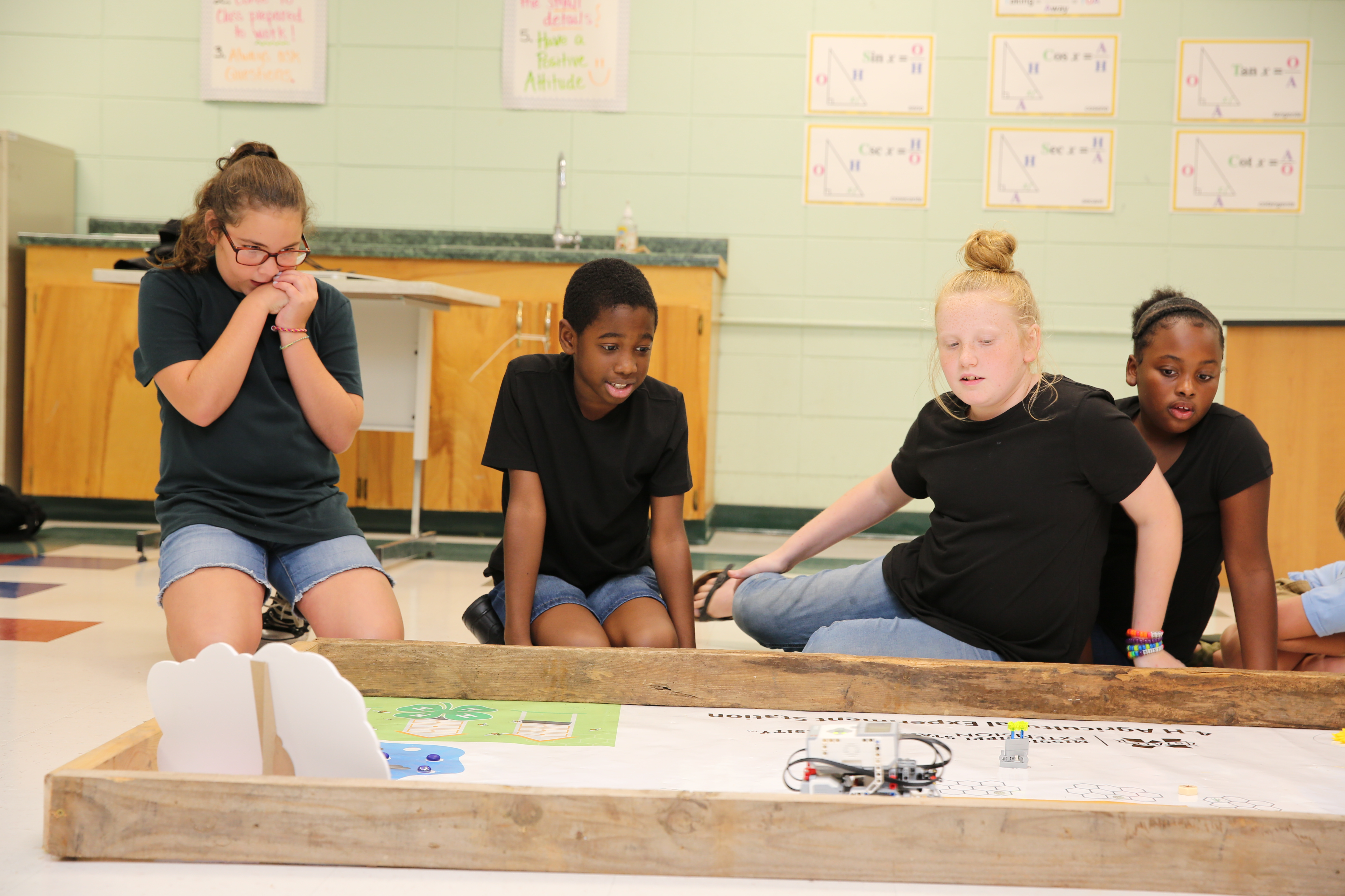 Three girls and one boy wearing black shirts looking anxious as they compete in a robotics competition.