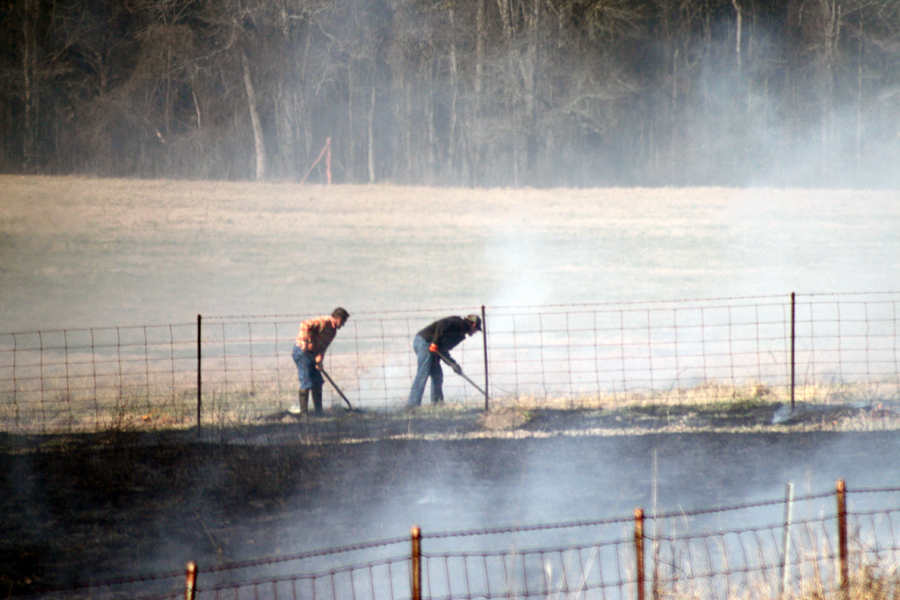 two men managing a smoldering field that has been burned