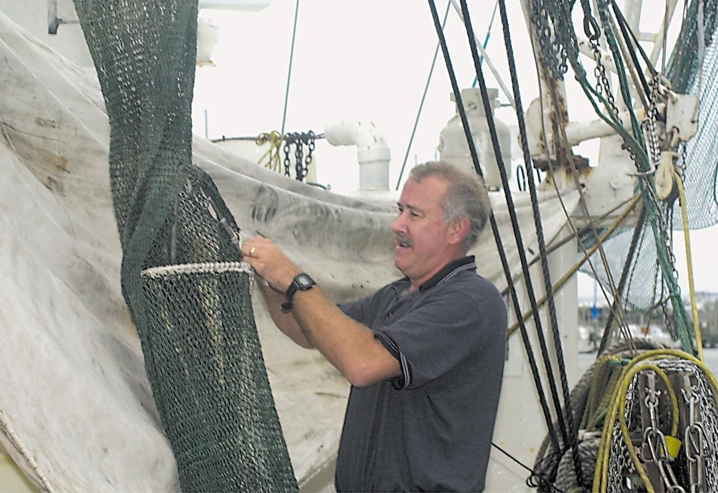 Marine resources specialist Dave Burrage  installs a bycatch reductions device into a shrimp net.