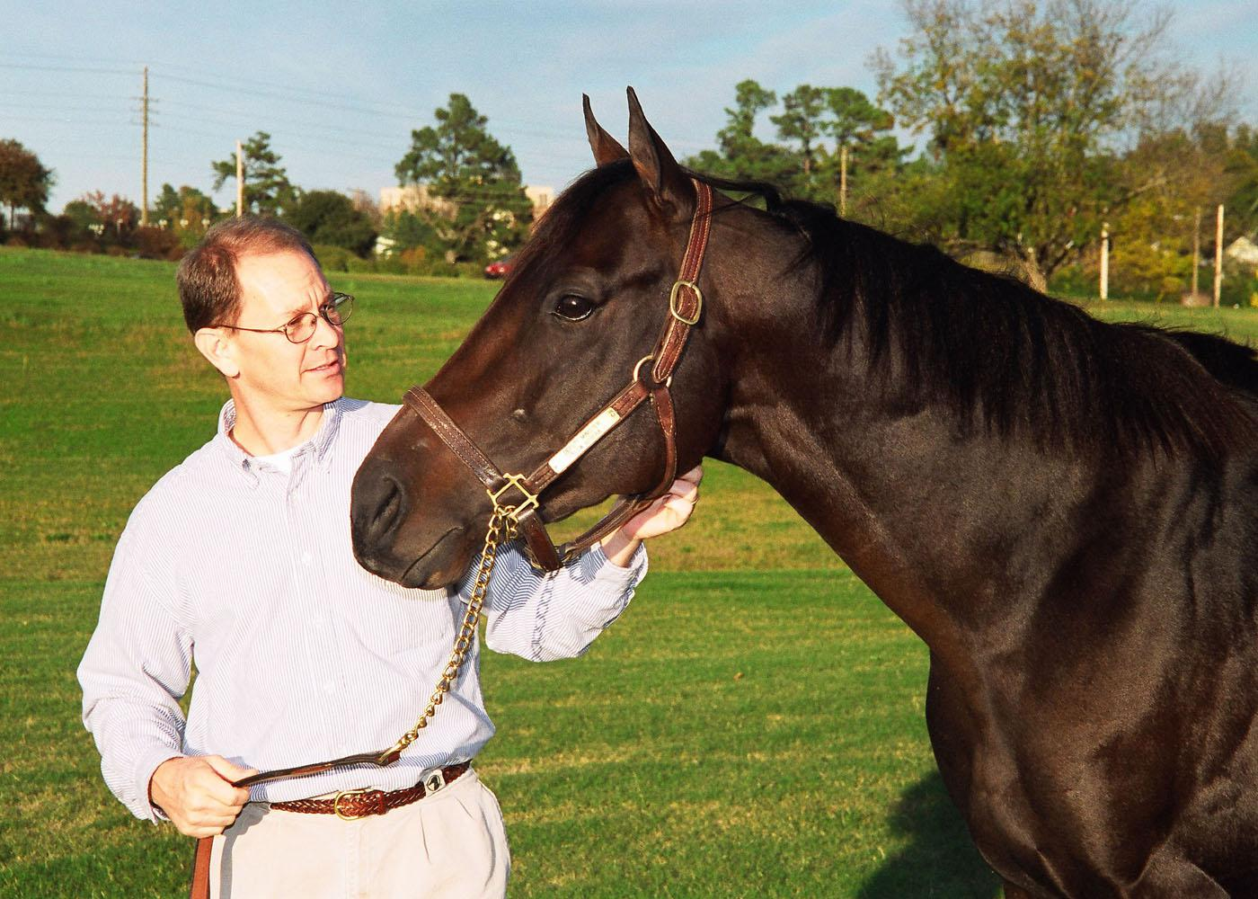 Dr. David Christiansen, a clinical instructor in Mississippi State University's College of Veterinary Medicine, holds Minister Slew, the grandson of Triple Crown winner Seattle Slew. The university is offering Minister Slew and four other stallions for stud services to horse breeders around the region. (Photo by Linda Breazeale, MSU Ag Communications )