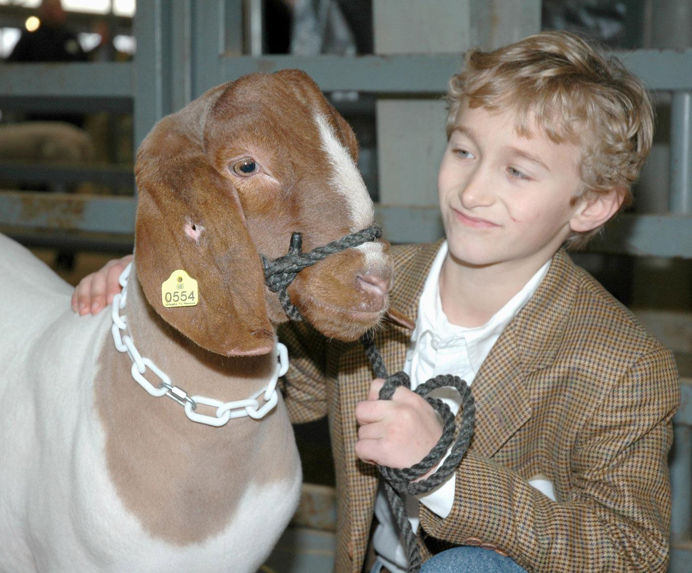 Tate County 4-H member Canan McKellar, age 9, spends a moment with his grand champion goat before entering the arena at the Dixie National Sale of Junior Champions. The goat, which was the champion mediumweight goat, brought a sale record $80 per pound for a total of $7,200.