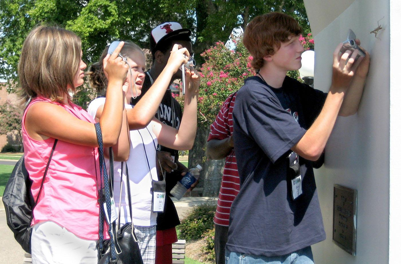 4-H Technology Conference participants, from left, Tara Roberts and Shelly Guy, both of George County, and Devin Doole of Marshall County focus their cameras on a praying mantis during a photo safari. They were taking part in the digital photography track during the three-day camp held at Mississippi State University. (Photo by Jim Lytle/Mississippi State University Ag Communications)