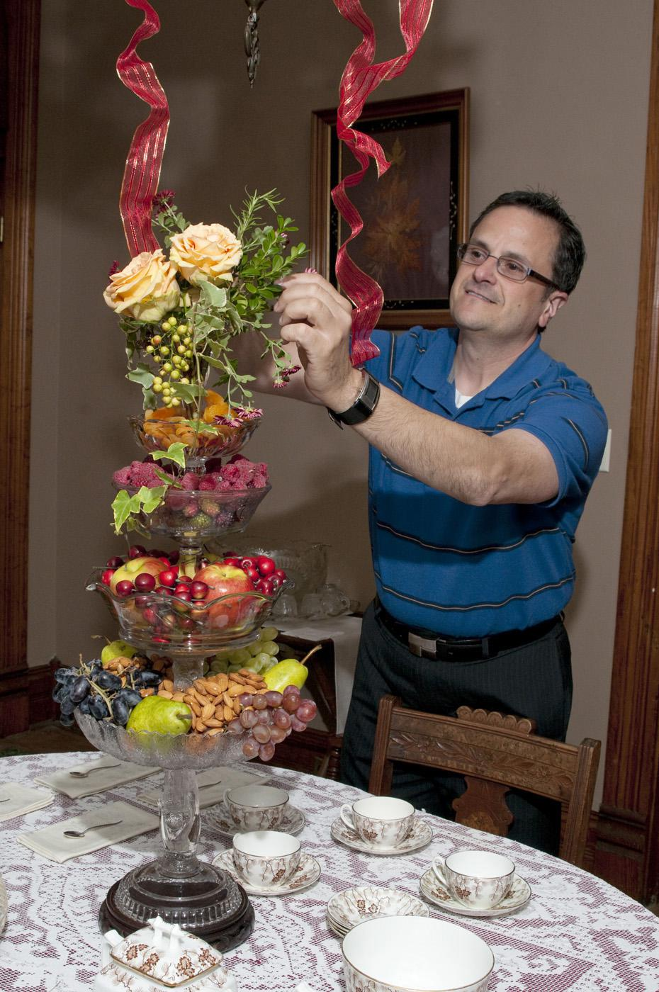 Jim DelPrince fills stacked glass comports with fruit, nuts and cut plant materials to create a stunning but inexpensive holiday centerpiece. (Photo by Scott Corey)