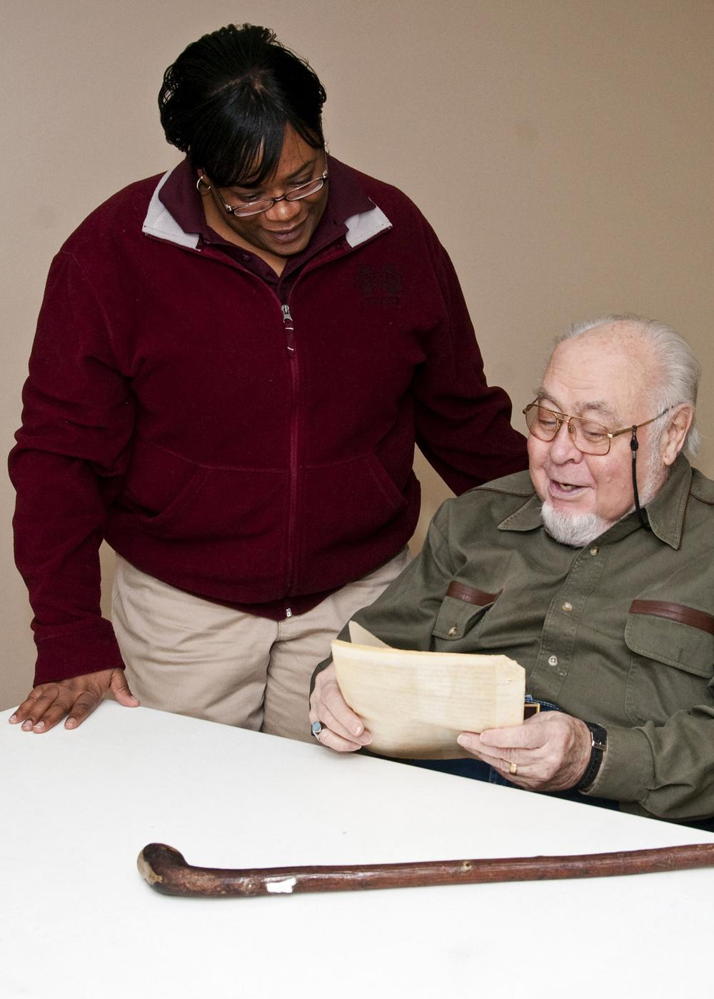 Clay County 4-H agent Fran Brock and volunteer leader Norman Armstrong look over one of his old scripts from a radio program he did as a member and leader to promote 4-H involvement. (Photo by MSU Ag Communications/Scott Corey)