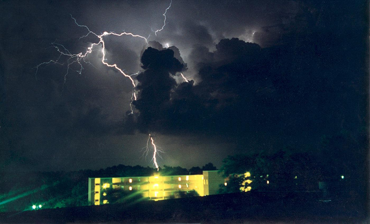 A brilliant streak of lightning flashes over Suttle Hall, north of Mississippi State University, during a summer storm in this archived photo. (Photo by MSU Geosciences/Michael Brown)