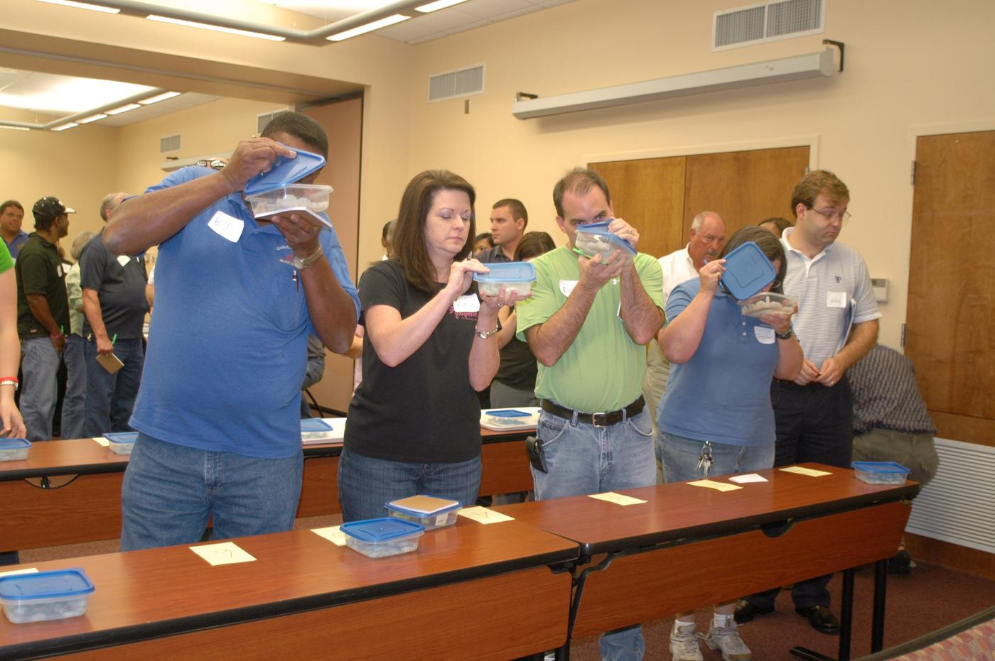 Participants in a recent Harvest from Open Waters training in Biloxi line up to sniff samples of shrimp and grouper spiked with oil in concentrations as low as 5 parts per million and less. (Photo by Karen Templeton)
