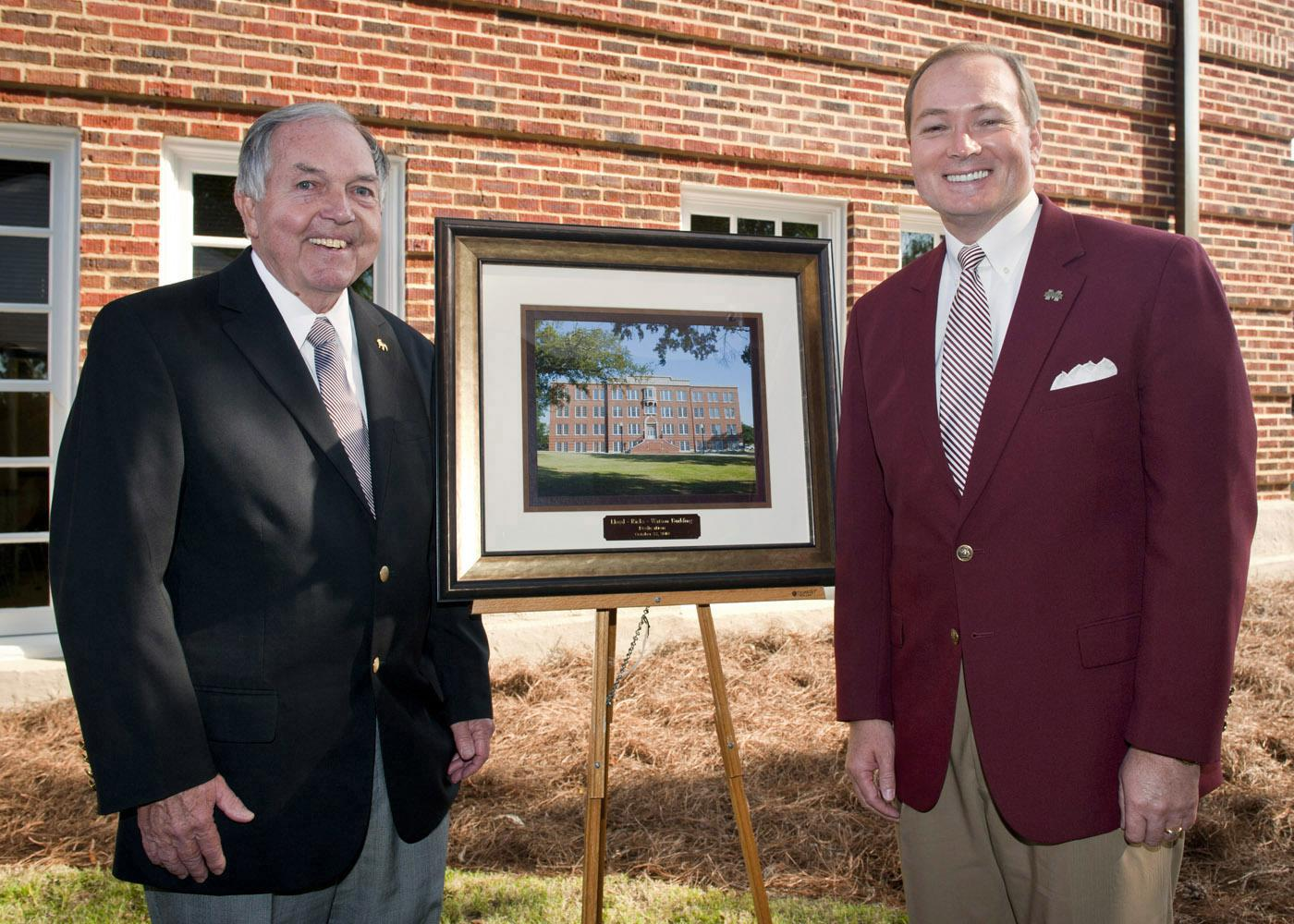 The newly renovated and renamed Lloyd-Ricks-Watson building at Mississippi State University was dedicated on Oct. 23. Vance Watson, left, one of the buildings' namesakes, receives a photo of the building from MSU president Mark Keenum. (Photo by MSU University Relations/Russ Houston)