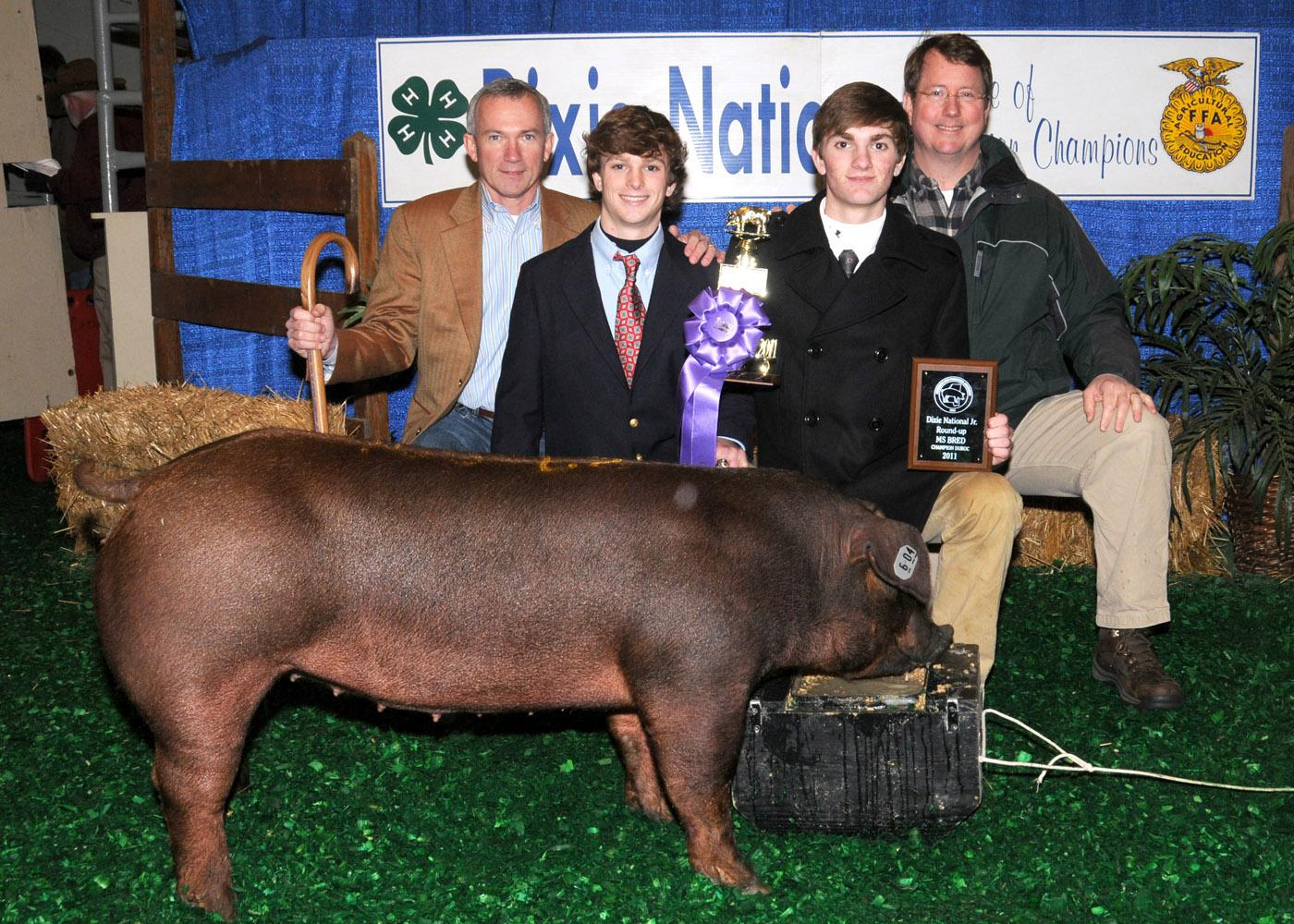 John Lundy (back left) and Eric Clark (back right) along with First South Farm Credit, Wilson's Meat House, Cecil Harper, Kipp Brown and Jim Newsome purchased a Champion Durac Hog from Tanner Ainsworth (front left) and Cory Ainsworth (front right) at the 2011 Dixie National Sale of Junior Champions. The buyers donated the meat to the Leroy Shook family. (Photo by Scott Corey)