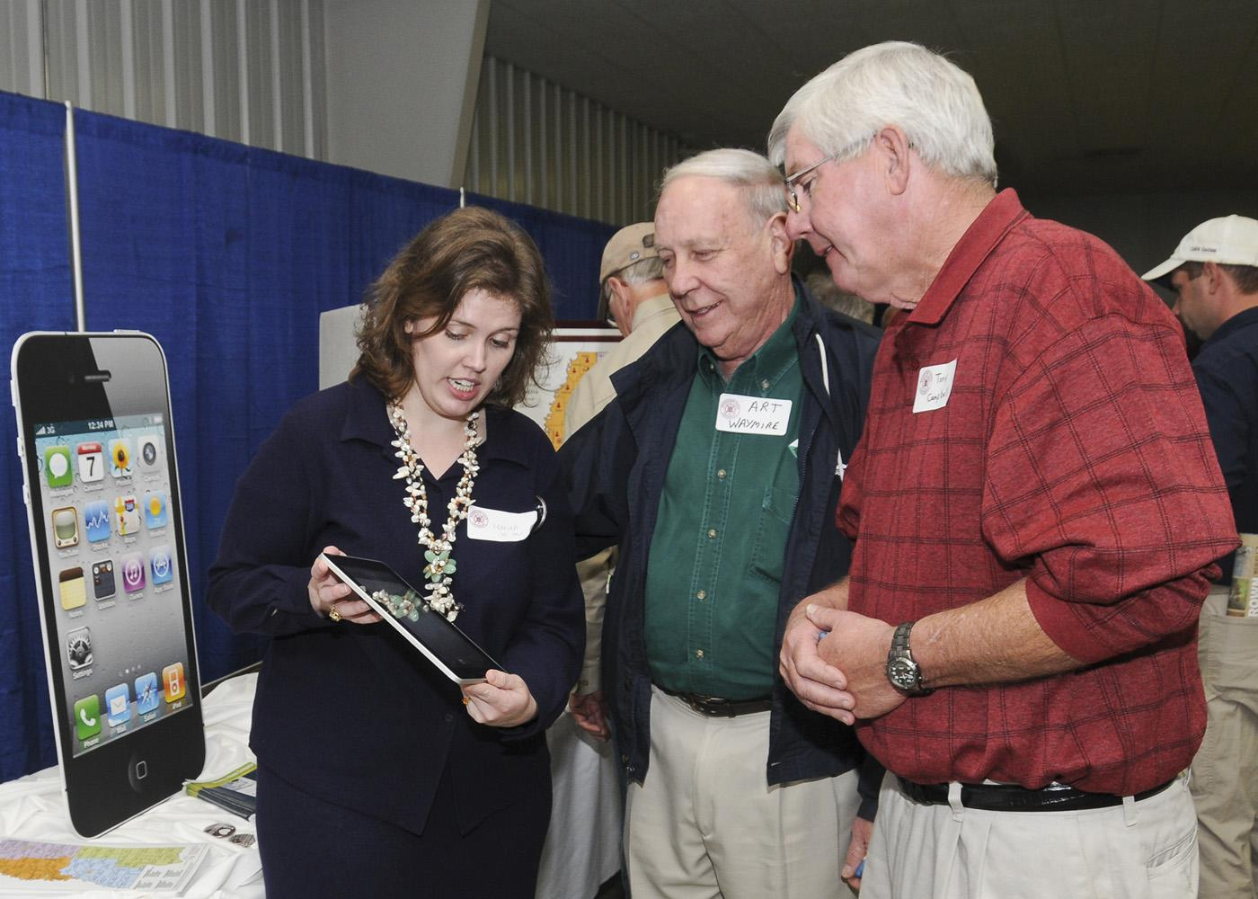 Mariah Smith (left), Extension computer applications instructor, discusses the iPad and its use in agricultural production with Art Waymire (center), a tree farmer from Marshall County, and Tony Campbell, a cotton and soybean farmer from Itawamba County. (Photo by Scott Corey)