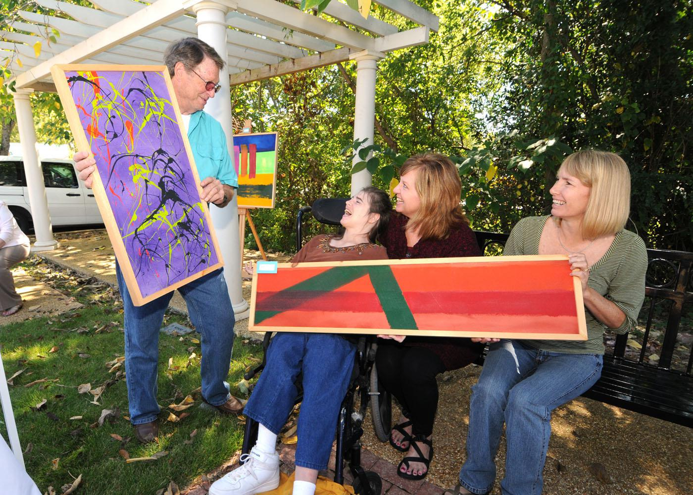 """Chickasaw County Master Gardener President John Walden, left, visits with """"EXPRESS Yourself"""" artist Amanda Williams of Ackerman during the Art in the Park event in downtown Houston. Judy Duncan and Barbara Boydston of the T.K. Martin Center at Mississippi State University brought artwork and clients to the event, which was co-sponsored by the Master Gardeners, the Mississippi Homemaker Volunteers and the MSU Alumni Association's Chickasaw County chapter. (Photo by Scott Corey)"""