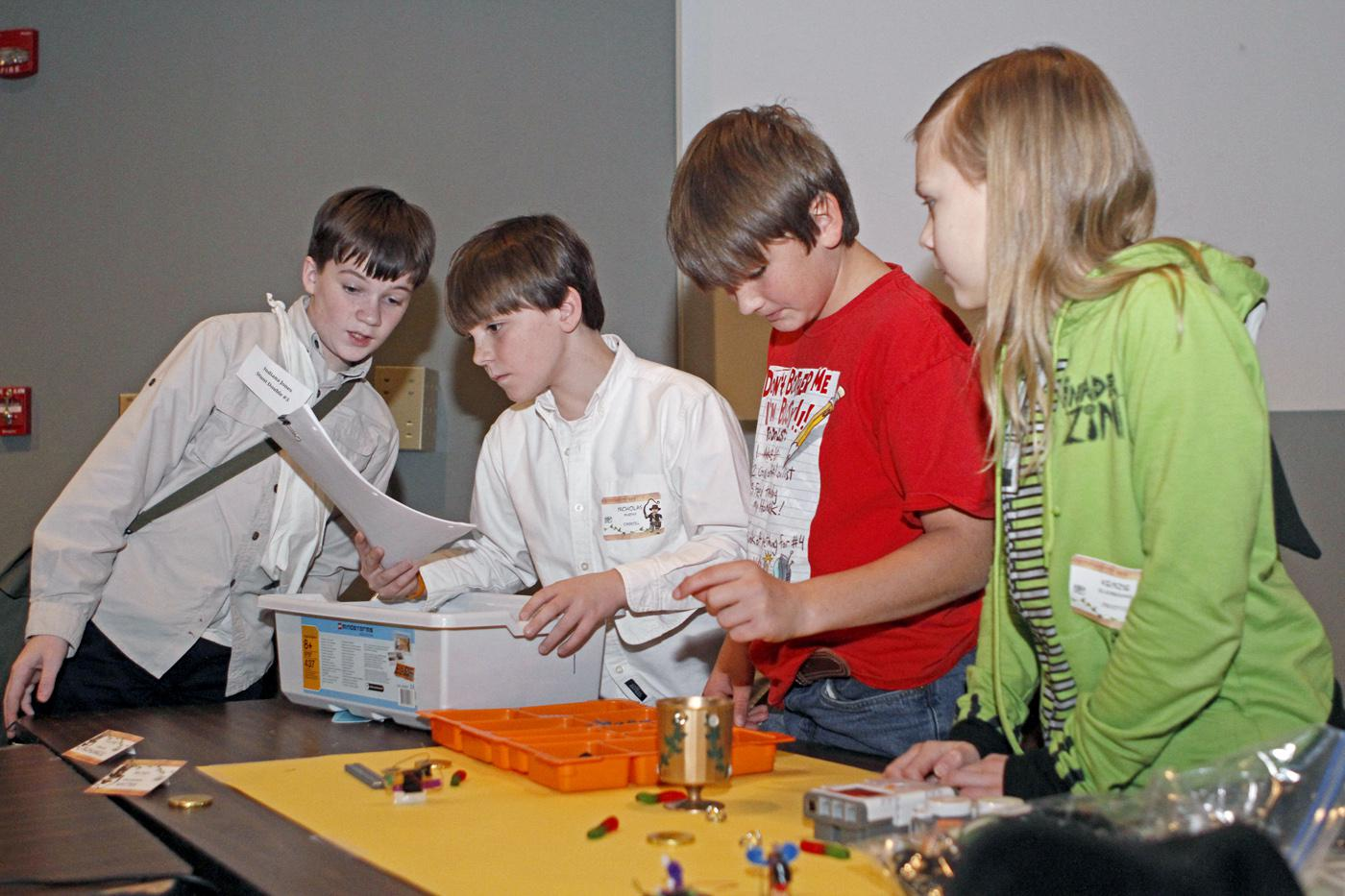 """Jonathan Rodgers of DeSoto County, from left, Nick Murphy of Carroll County, Austin """"Bubba"""" Meriweather of Leflore County and Kenzie Ellenberger of DeSoto County follow instructions to build a robot. The four joined other 4-H youth, volunteer leaders and agents at the recent kick-off of the 2012 robotics project at Mississippi State University. (Submitted Photo)"""