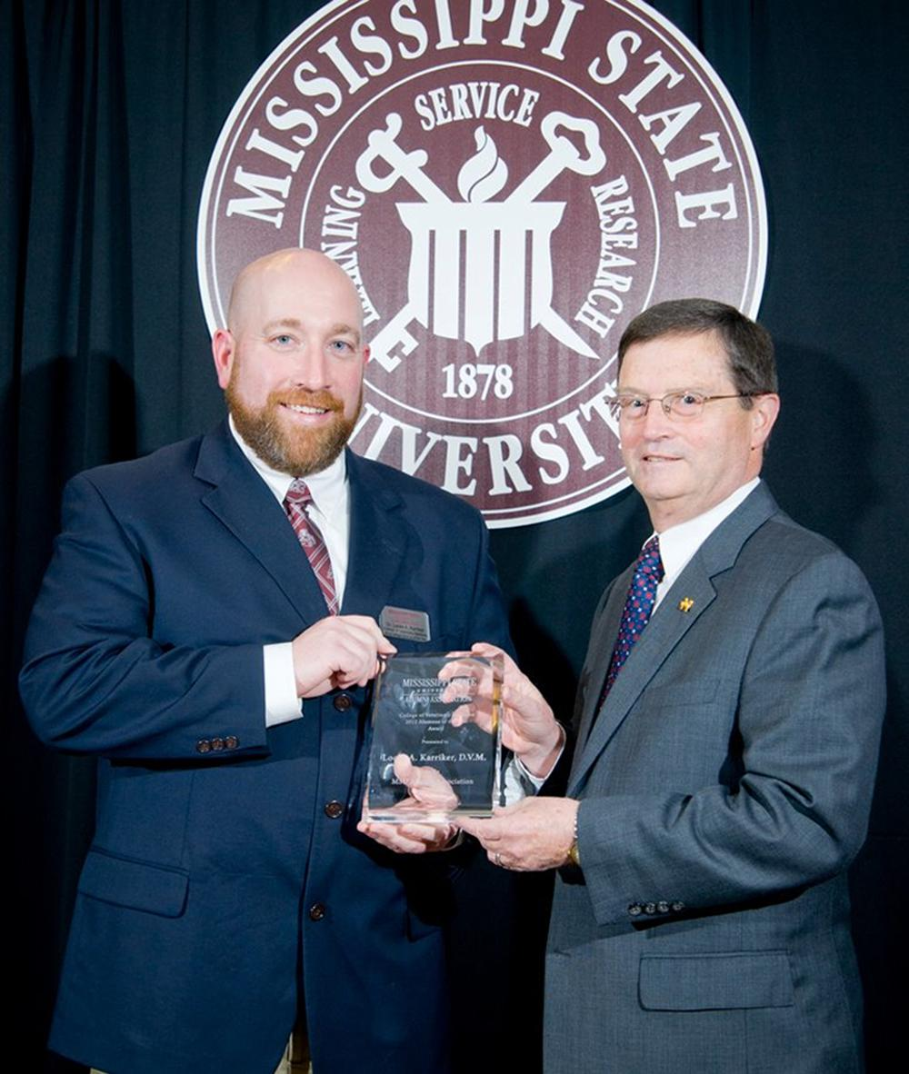 Dr. Locke Karriker, director of the Swine Medicine Education Center at Iowa State University, left, receives the 2012 College of Veterinary Medicine Alumnus of the Year award at Mississippi State University from Dr. Kent Hoblet, the college's dean. (Photo by MSU University Relations/Russ Houston)