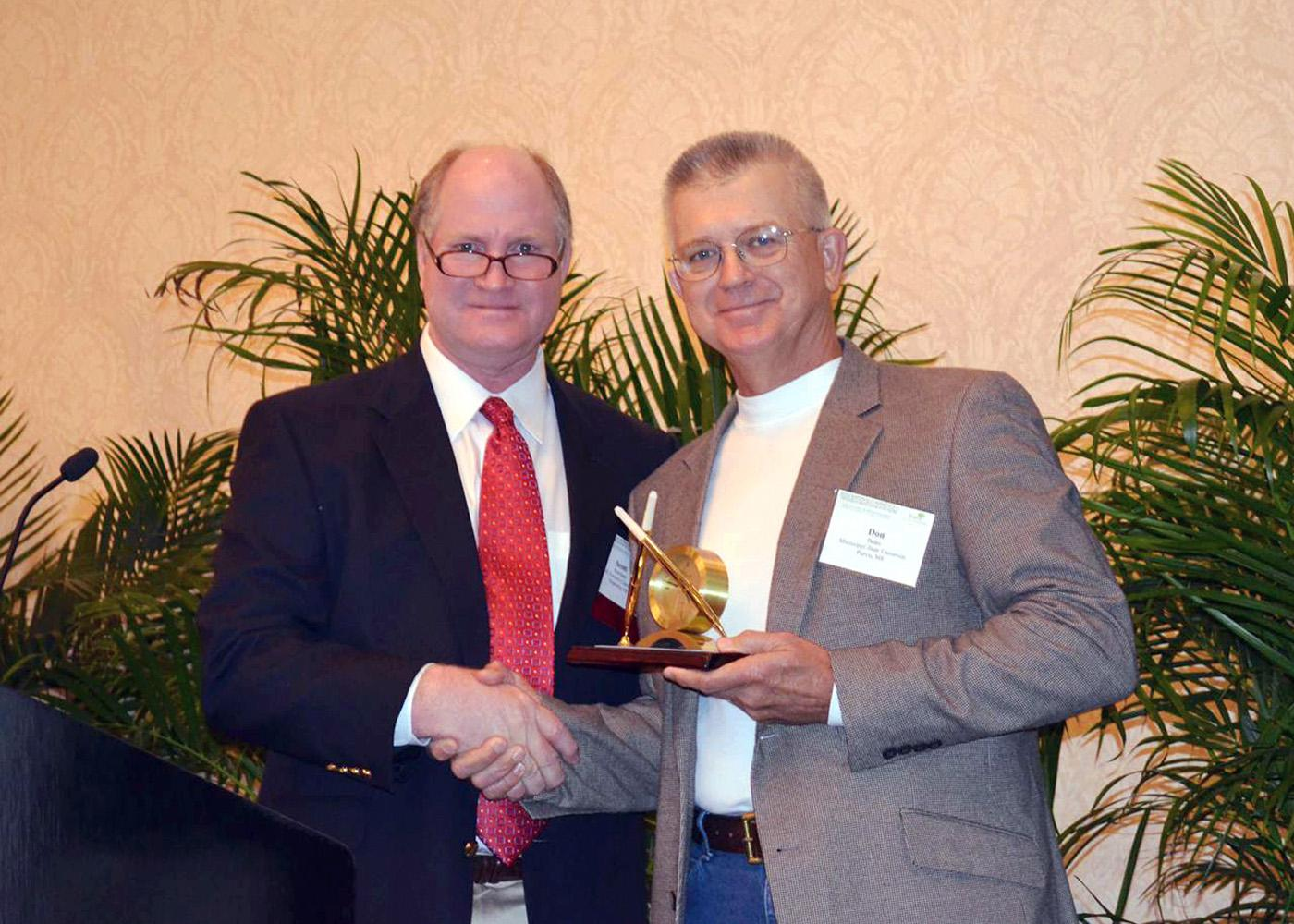 Scott Rowland, South Central regional vice president of the Forest Landowners Association, presents their Extension Forester of the Year award to Don Bales of Purvis, a forest and wildlife management specialist with Mississippi State University's Extension Service. (Submitted Photo)