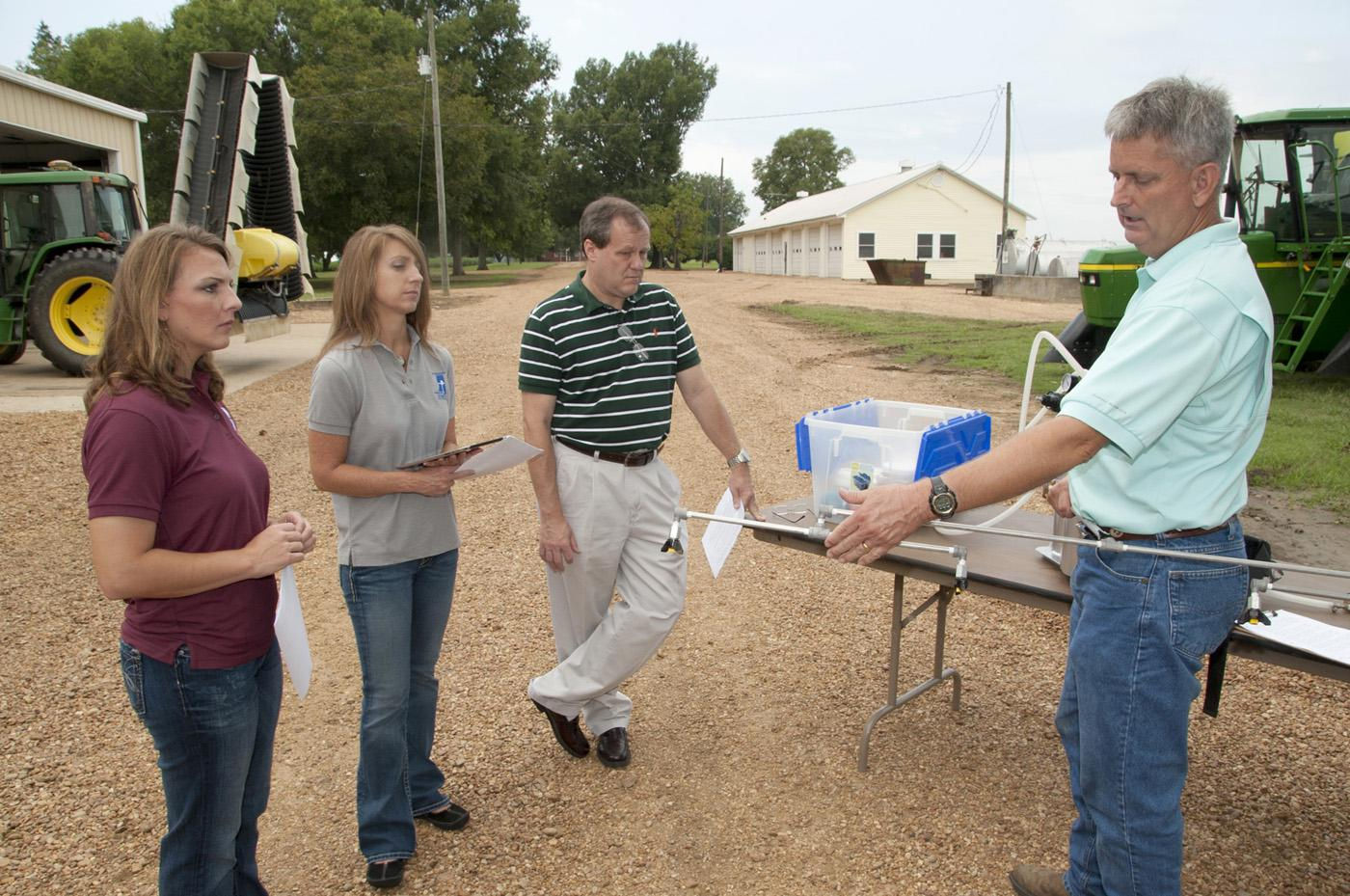 A Mississippi State University Extension Service team gets acrash-course in how sprayers work from Dan Reynolds. From left, Jamie Varner, Kelli McCarter andRandy Loper are writing an app that will help farmers properly calibrate sprayers. (Photo by MSU Ag Communications/Kat Lawrence)