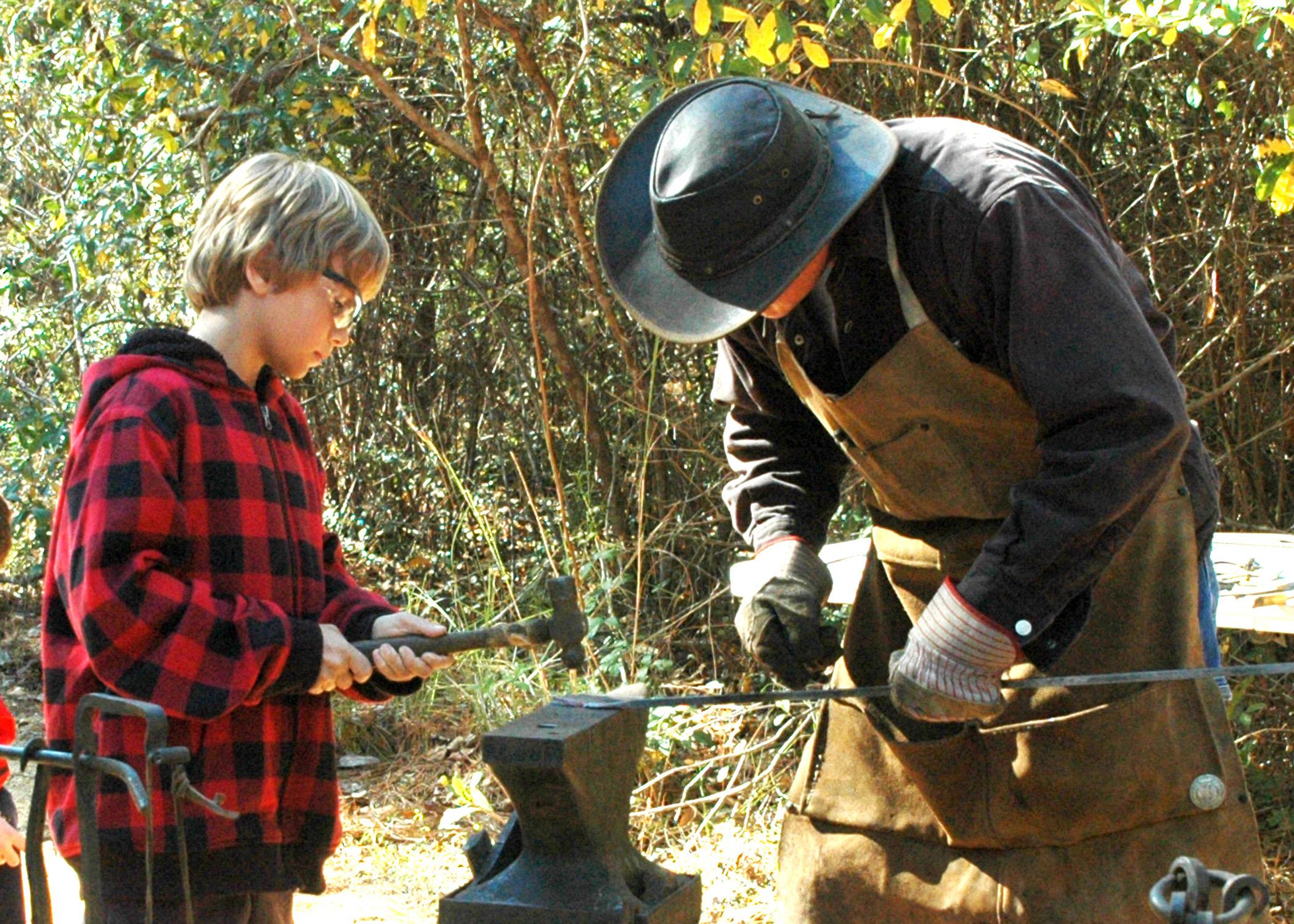 Fourth-generation blacksmith Chuck Averett helps Morgan Alexander make an arrowhead at the Piney Woods Heritage Festival held Nov. 16 and 17 at Mississippi State University's Crosby Arboretum. (MSU Ag Communications/Susan Collins-Smith)