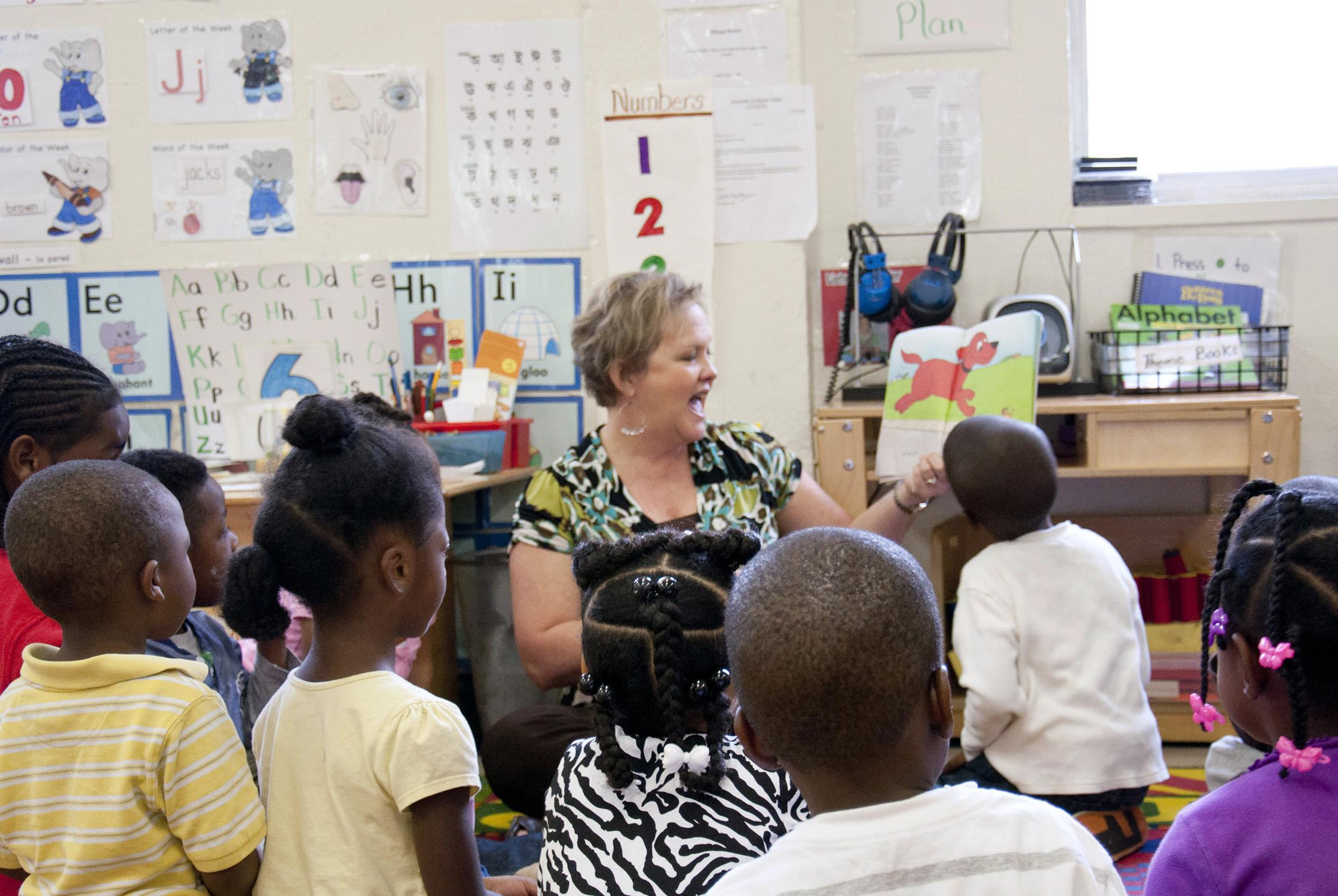 Melissa Tenhet, project director for the Mississippi Child Care Resource and Referral Network shares a story with the preschool students at the Brickfire Project after completing literacy pre-assessments through Starkville Rotary's community service project. (Photo by MSU Extension Service/Alicia Barnes)
