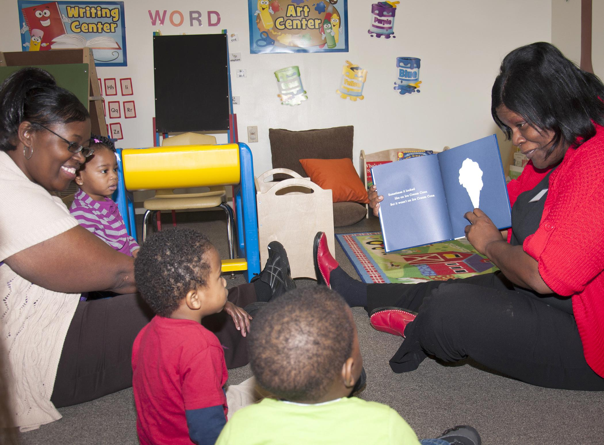 From left, Brenda Wright, owner of Heavenly Hearts Learning Center in Nesbit, joins Schmaya Miller, Kingston Jenkins and Ken'Narius Johnson to listen as LaLetrice Fletcher, field technical assistant with the Nurturing Homes Initiative, reads them a book. (Photo by MSU Extension Service/Alicia Barnes)