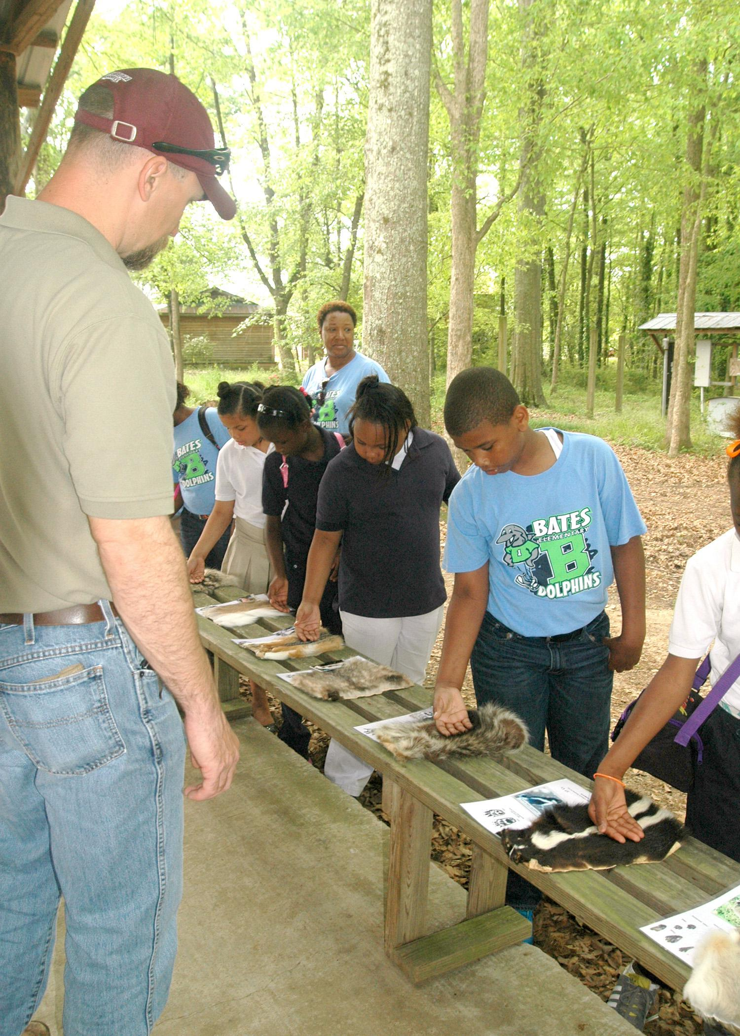 Ty Jones, county coordinator with Mississippi State University's Extension Service in Madison County, looks on as Bates Elementary fourth-graders feel the pelts of wild animals native to Mississippi, such as the skunk and raccoon. The display was part of the Extension-sponsored AgVentures at the Mississippi Agricultural and Forestry Museum in Jackson April 16 and 17. (Photo by MSU Ag Communications/Susan Collins-Smith)