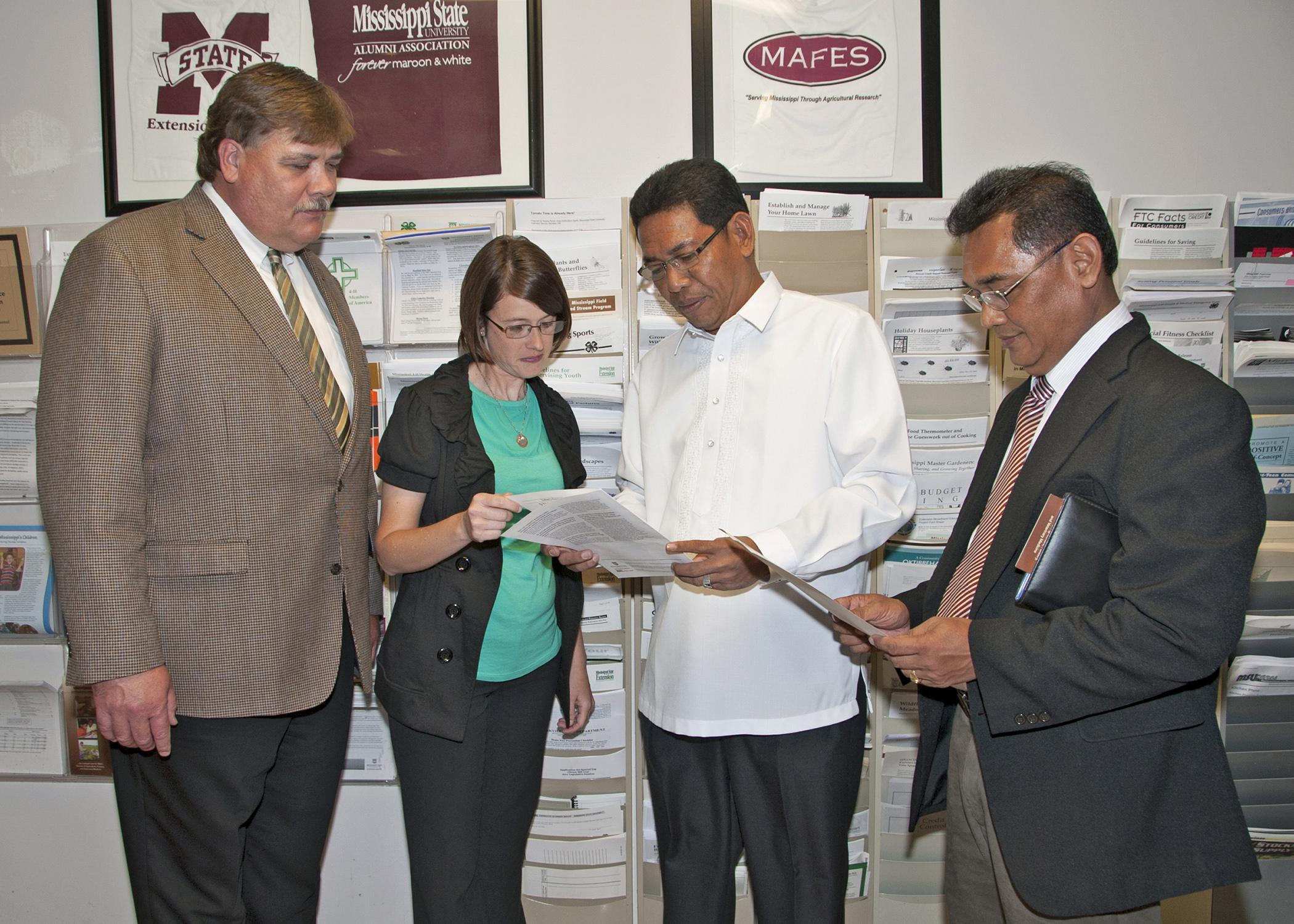 Mississippi State University Extension Service Director Gary Jackson and Oktibbeha County Extension Coordinator Julie White review some of the many publications available through Extension with Edilberto DeLuna and Asterio Saliot, members of an agricultural delegation from the Philippines, visiting the county office on May 28, 2013. (Photo by MSU Ag Communications/Kat Lawrence)