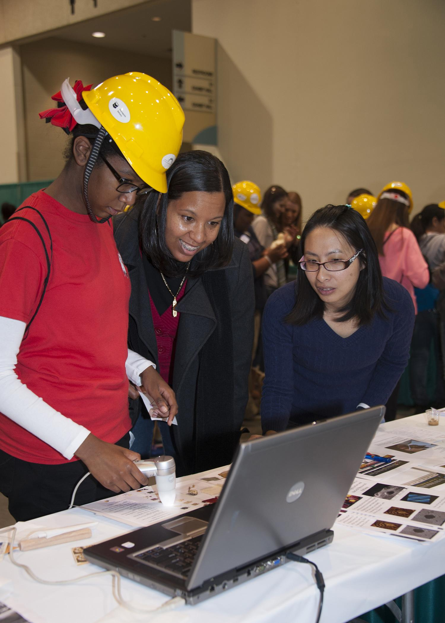 I-Wei Chu, with Mississippi State University's Institute for Imaging and Analytical Technologies, helps Biloxi Junior High School eighth-grader, Danaisha Cherry, and her mother, Lydia Cherry, look at some images with a scanning electron microscope during the Pathways2Possibilities career expo Nov. 13. More than 6,000 eighth-graders participated in the two-day event at the Mississippi Coast Coliseum and Convention Center in Biloxi. (Photo by MSU Ag Communications/Kat Lawrence)