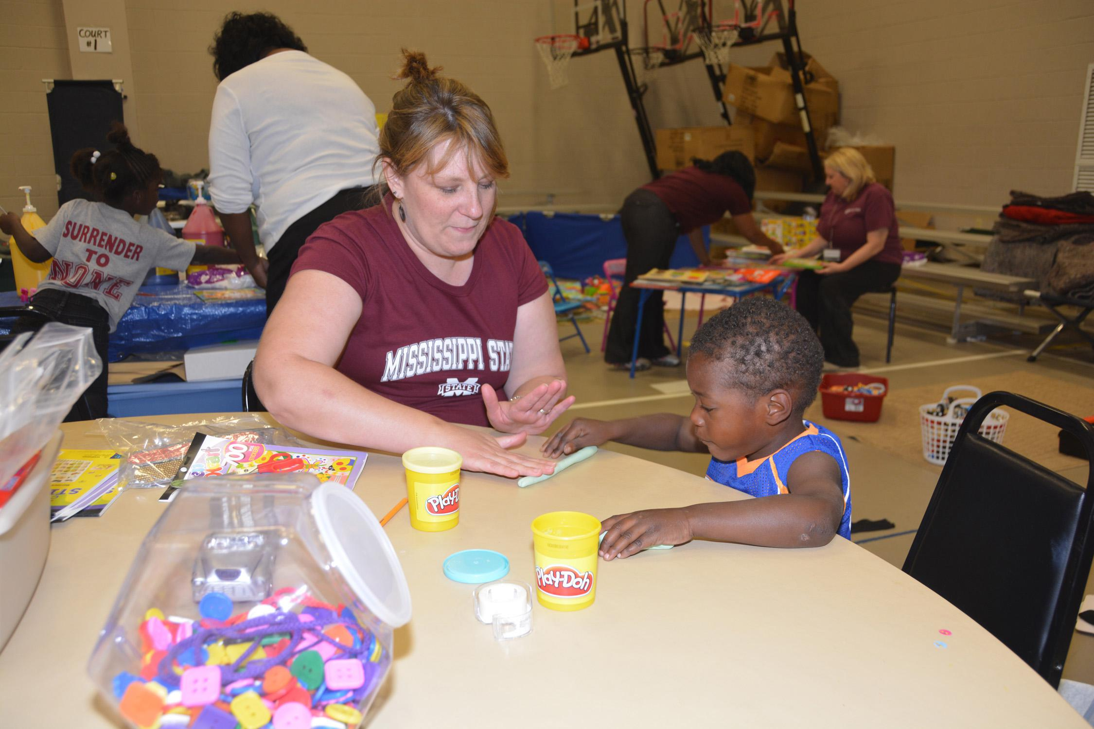 Gina Carr, a Mississippi State University Extension Service staff member with the Mississippi Child Care Resource and Referral Network, keeps 3-year-old Brandily Haynes engaged while his family is in the American Red Cross Shelter at First Baptist Church in Louisville, Mississippi, on May 1, 2014.  (Photo by MSU Ag Communications/Linda Breazeale)