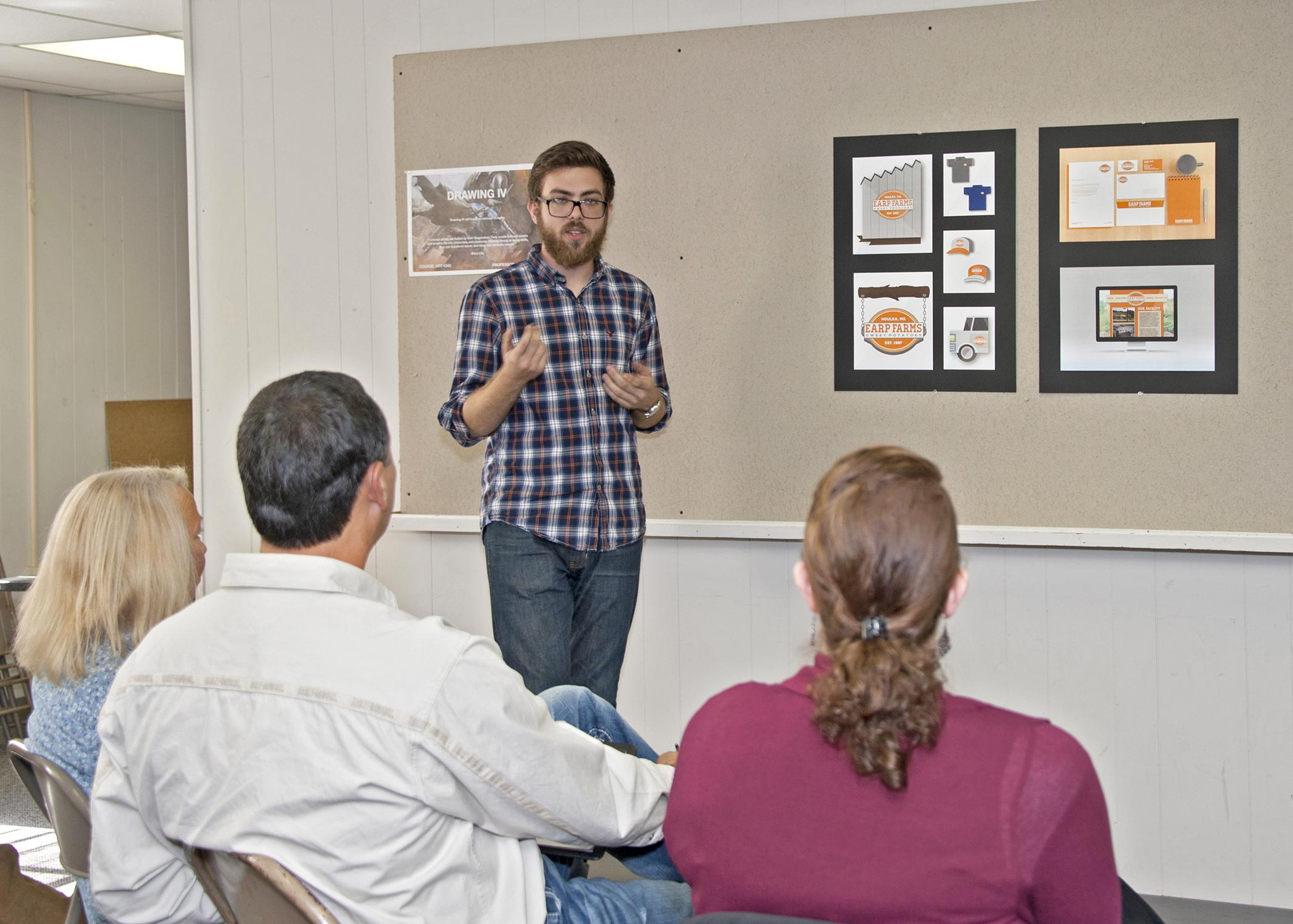 On Nov. 6, 2014, Austin Edwards, a Mississippi State University senior graphic design major from Gulfport, explains his concept in class for a new brand image for Earp Farms in Houlka. (Photo by MSU Ag Communications/Kat Lawrence)