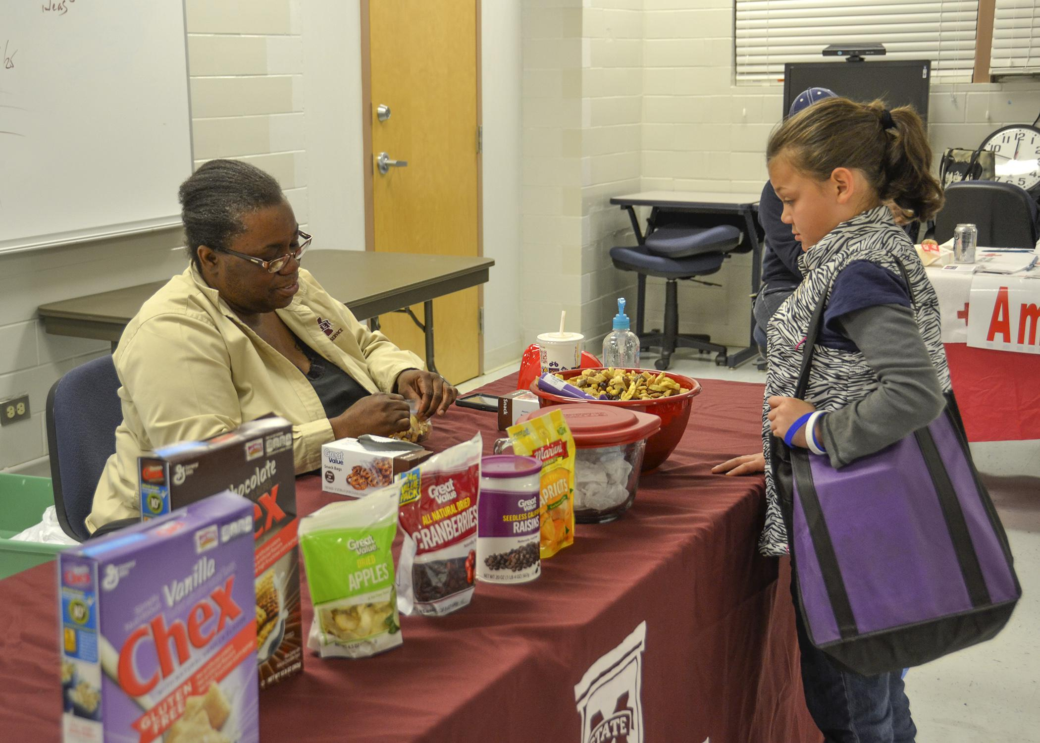 Mississippi State University Extension Service Child and Family Development agent Terri Thompson, left, gives Isabella Cornish a sample of an easy-to-make snack mix. The MSU Extension Service was one of several organizations participating in the Super Saturday healthy cooking event in Pascagoula, Mississippi on Nov. 15, 2014. (Photo by MSU Extension Service/Susan Collins-Smith)