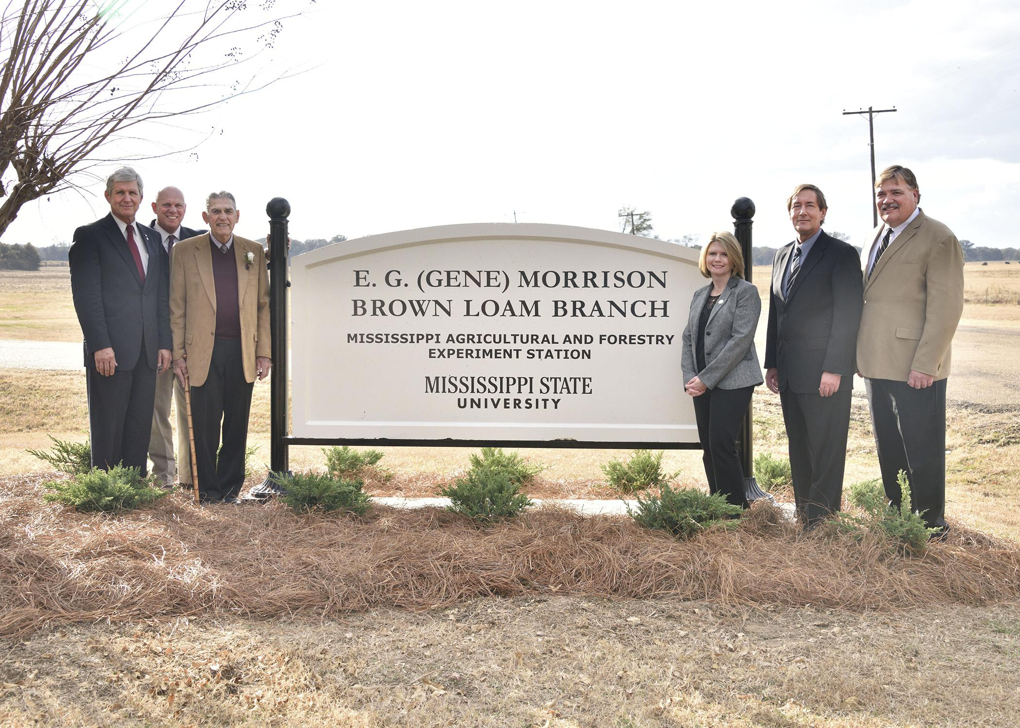 "The Mississippi State University Brown Loam Branch Experiment Station was renamed in honor of E.G. ""Gene"" Morrison on Nov. 20, 2014, who served as its superintendent for 33 years. Morrison, third from left, is pictured with the new sign along with Mississippi Senator Perry Lee, far left; Mississippi Agricultural and Forestry Experiment Station director George Hopper; Central Mississippi Research and Extension Center Head Sherry Surrette; Vice President for the Division of Agriculture, Forestry and Veterinar"